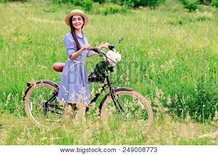 Pretty woman biker in a summer field