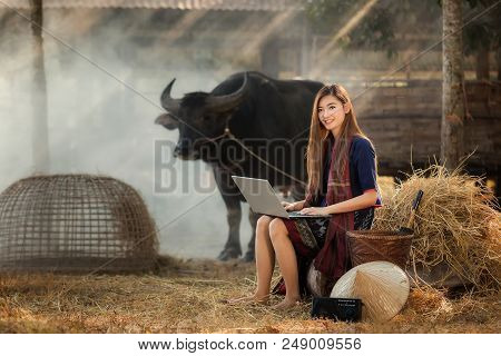 Portrait Of A Beautiful Rural Woman,rural Woman Playing Computer Notebook On Her Farm Background In