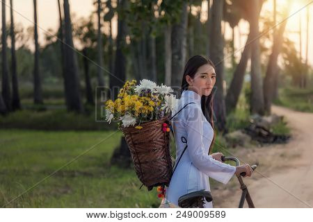 Woman wearing a Vietnamese dress Ao Dai are ride on a bicycle along the road in a village at countryside,Woman Vietnam ride on a bicycle. poster