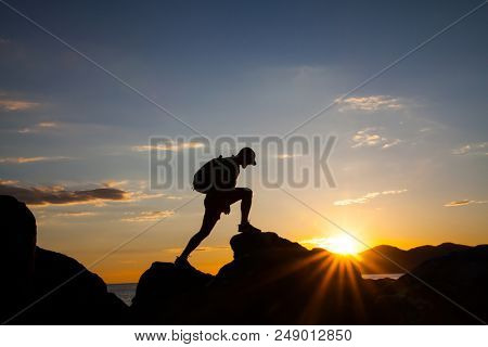 Silhouette of  a traveler hiking on mountain at sunset.Freedom, risk, challenge, success concept.