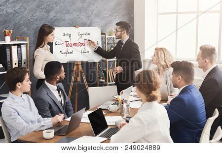 Foreign partner making presentation about teamwork to business team, female interpreter helping him. Teambuilding training in company poster