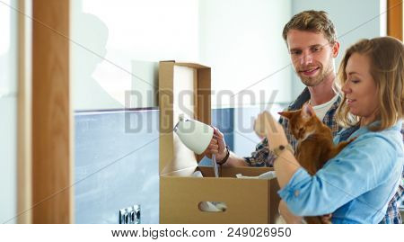 Young couple carrying big cardboard box at new home.Moving house. Young couple