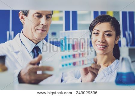 Talking to assistant. Elderly experienced famous chemist feeling involved in talking to his young assistant poster
