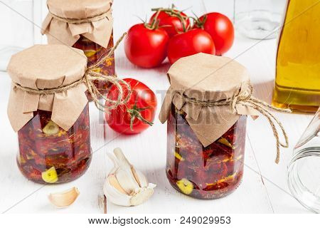 Sun-dried Tomatoes With Extra Virgin Olive Oil, Garlic And Herbs In Glass Jars Close-up