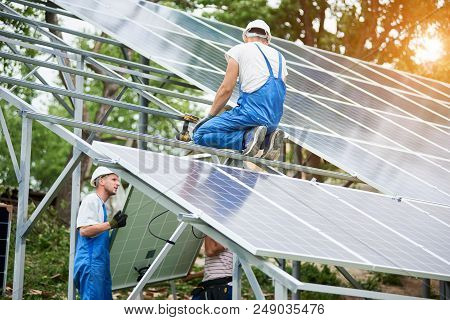 Team Of Three Technicians Mounting Photo Voltaic Panel To Stand-alone Solar System Platform On Brigh