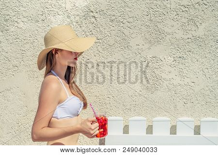 Summertime. Young Woman With Sunglasses, Red Cocktail And Floppy Hat.