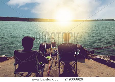 Rear Of Two Men On Seat Relax From Work With Fishing On Pier At Sea In Sunrise, Jeju Island, South K