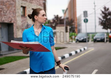 Young Girl With Folders For Papers And A Cup Of Coffee Is Standing On The City Street. Business Lady