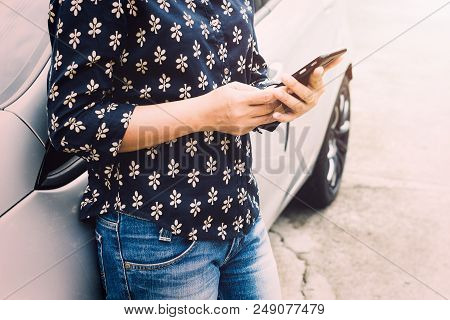 Woman Is Using Smart Phone To Find Directions Beside Hers Car.