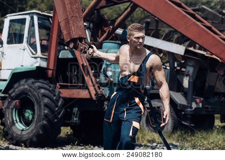 Power Concept. Power Man Pull Tractor With Crane. Power Lifter At Construction Site. Feel The Power.