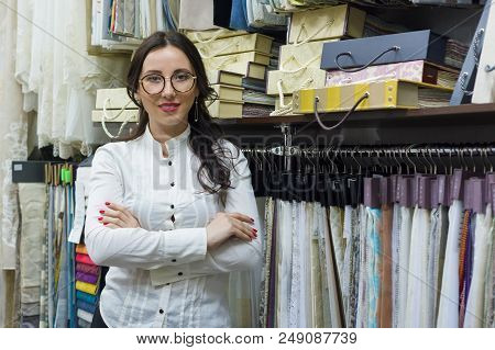 Portrait Of Happy Woman Owner With Crossed Arms In Interior Fabrics Store, Background Fabric Samples
