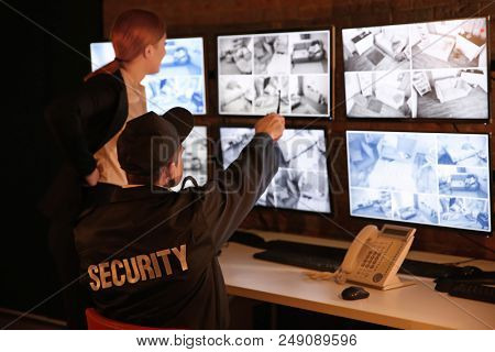 Security guards working in surveillance room