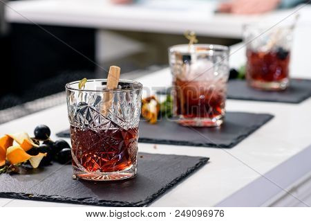 Line Of Classic Alcoholic Godfather Cocktails In Rocks Glasses At A Bar