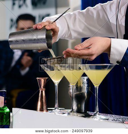 Unidentified Barman Adding Liquid In A Martini Glass