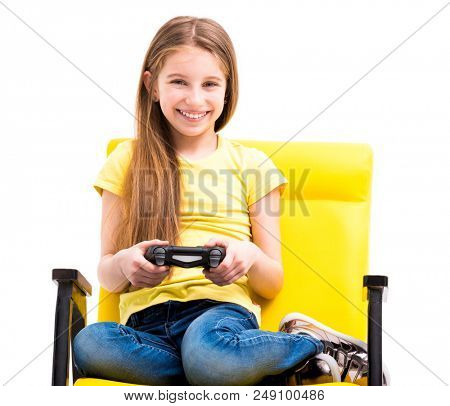 Pretty teen girl sitting, holding black joystick, playing console for computer games