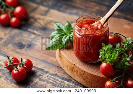 Homemade tomato sauce in a glass jar, tomatoes and herbs on its side.
