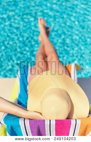 Summertime In Pool. Young Woman With Floppy Hat Lying In A Deck Chair By The Pool.