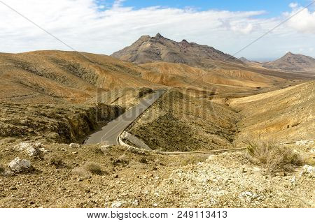 Typical Landscape Of Fuerteventura With Barren Volcanic Mountains And Winding Roads In The Wildernes