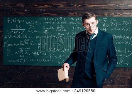 Exacting Teacher. Teacher Formal Wear And Glasses Looks Smart, Chalkboard Background. Man With High
