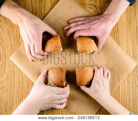 Fast Food Restaurant. Unidentified People Eating Tasty Sliced Burger. Top View, Flat Lay