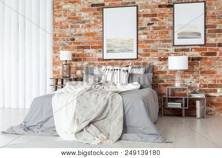 Posters On A Bare, Orange Brick Wall, Above A Cozy Bed With Gray Sheets In An Industrial Bedroom Int