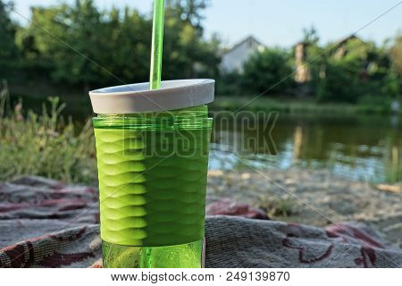 Plastic Green Glass With A Drink And A Tube On The Beach Near The Water