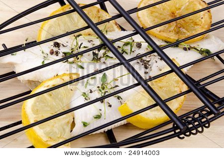 Plaice in a fish grill with tomato and lemon poster