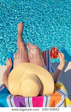 Summertime In Pool. Young Woman With Floppy Hat And Cocktail Lying In A Deck Chair By The Pool.