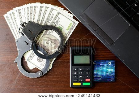 Steel Police Handcuffs, Bank Card, Money Dollars, Payment Device And Laptop Lying On Table, Top View