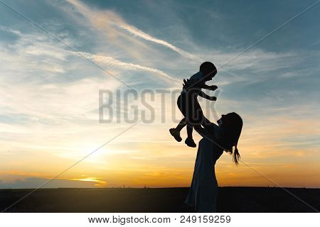 Silhouette Of Young Woman High Toss Up Little Cute Child Baby Boy On Nature, Sunset Horizon Backgrou