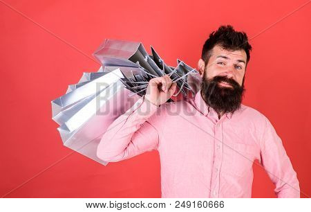 Man With Beard And Mustache Carries Shopping Bags On Shoulder, Red Background. Hipster On Cool Face