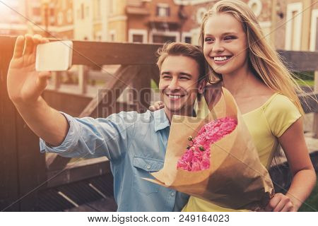 Romantic Young Couple Making Selfie Using Phone And Smiling While Sitting Outdoors. Beautiful Cute G