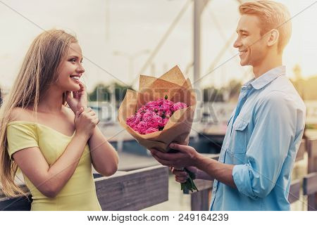 Handsome Young Man Gives Flowers To Beautiful Girl And Smiles. Couple Standing In Open Air. Bouquet