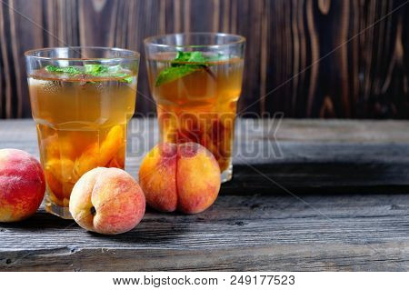 Peach Ice Tea In A Glass With Mint On Wooden Table, Closeup