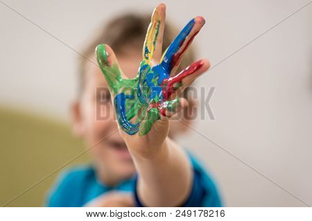 Happy Young Boy Doing Hand Painting Stretching His Hand Covered In Colourful Paint Towards The Camer