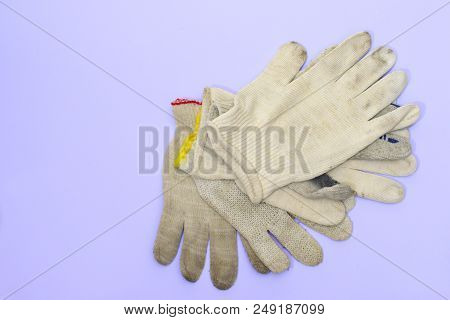 A Small Stack Of Simple Cloth Gloves For Manual Labor On A Purple-blue Background, With Clipping Pat