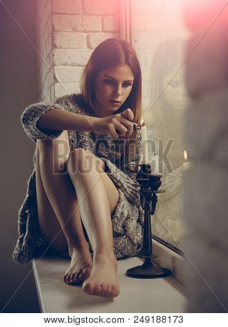 Beauty With Candles. Pretty Woman Light Candle On Window Sill. Fashion Woman With Makeup And Long Ha