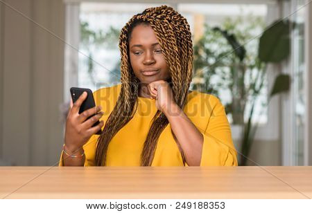 African american woman using smartphone serious face thinking about question, very confused idea