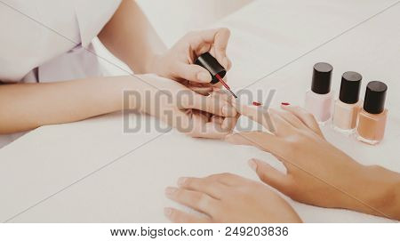 Drawing Of Red Varnish On Beautiful Natural Nails. Manicure In Beauty Salon. Spa Treatment. Young Wo