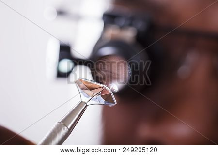 Macro Shot Of A Person Looking At Diamond With Magnifying Loupe