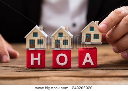 Businessperson Placing House Model Over Hoa Blocks
