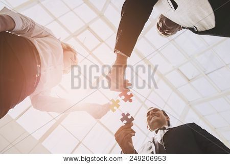 Three Smart Business Partners With Jigsaw Puzzles. Closeup Of Business People Wanting Put Three Piec