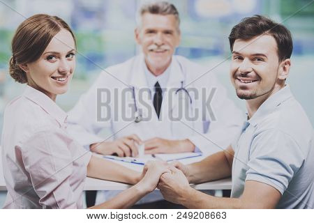 Happy Couple Sitting On Background Of Doctor. Man And Woman Holding Hands. At Doctor At Reception. B