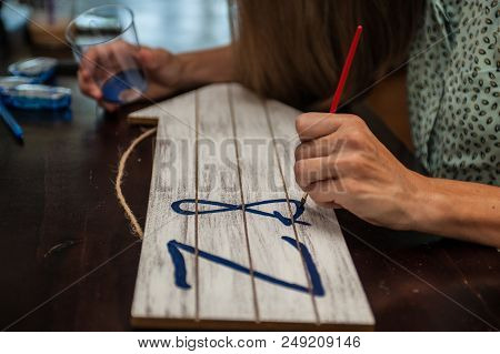 Talented Left Handed Artist Painting The Lettering For A Decorative Sign.