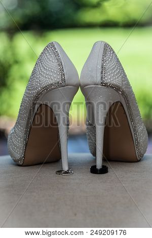 Stiletto High Heel Shoes Of The Bride Holding The Husband And Wife Wedding Rings In Place.