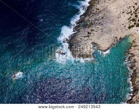 Aerial above rugged rocky coastline in stormy seas