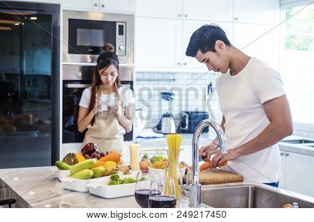 Beautiful Young Couple Is Cooking In Kitchen At Home.man Is Cooking With Moman Is Using A Digital Ta