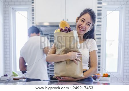 Beautiful Asian Young Couple Loving Smiling Is Looking To Cooking In Kitchen At Home, Woman With A B