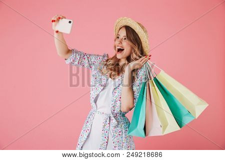 Image of surprised young woman standing isolated over pink background make selfie by mobile phone. Looking aside holding shopping bags.