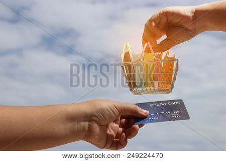 Hand Holding Basket Of Colorful Shopping Paper Bags And Another Hand Holding Mock Up Of Credit Card